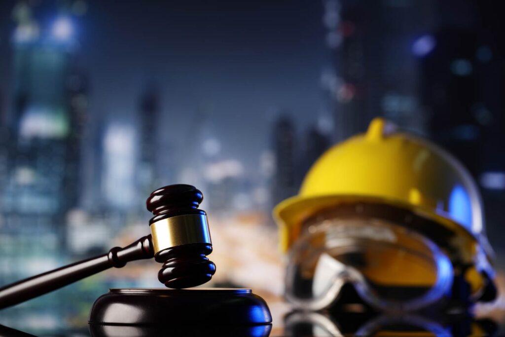 Sudski cekic na stolu pored slema za gradjevinske radnike